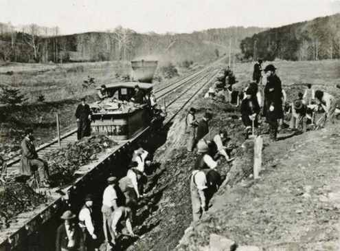 Men dig a hillside as a locomotive waits to haul the dirt - photo from Virginia.
